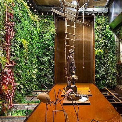 Green vertical jungle in a store design commercial interior design news mindful design - Vertical garden design ...
