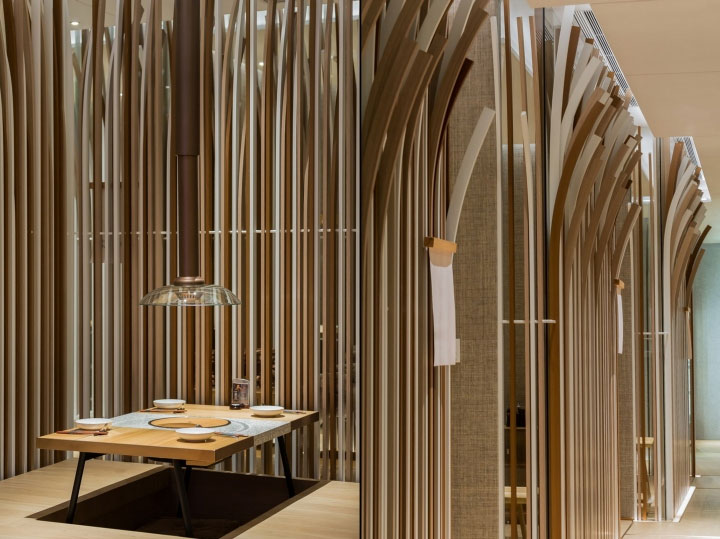 Dining rooms separated by tall wood strips to create intimate restaurant interior