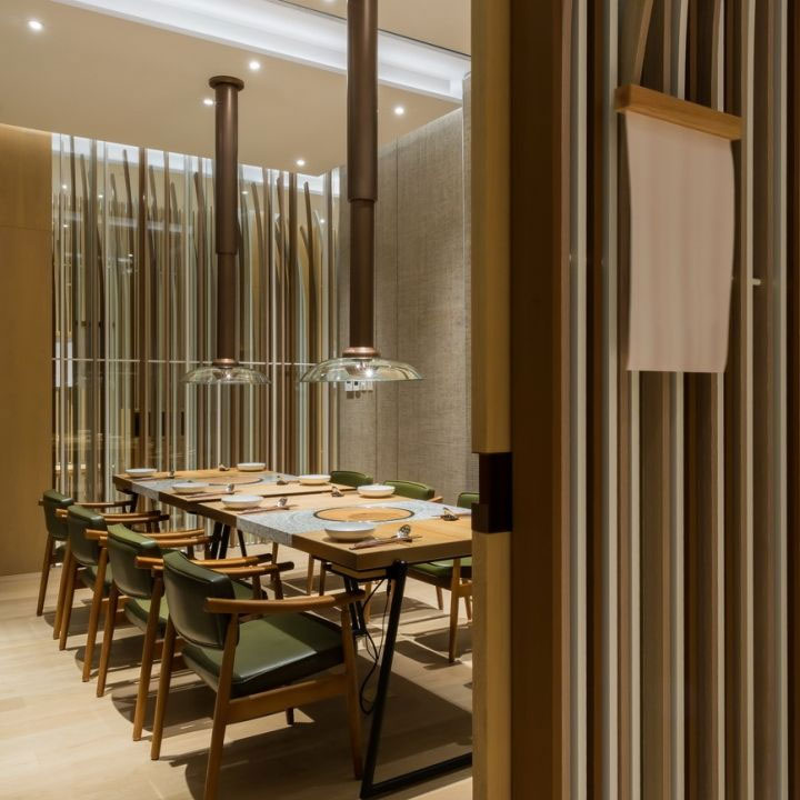 Private rooms divided by wood strip walls for cozy restaurant interior