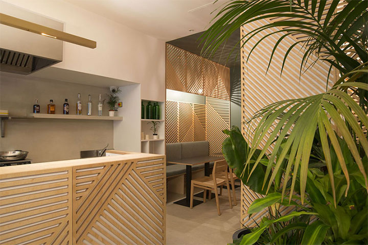 Interior of Indonesian restaurant with wood-panel geometric patterns on walls and counter