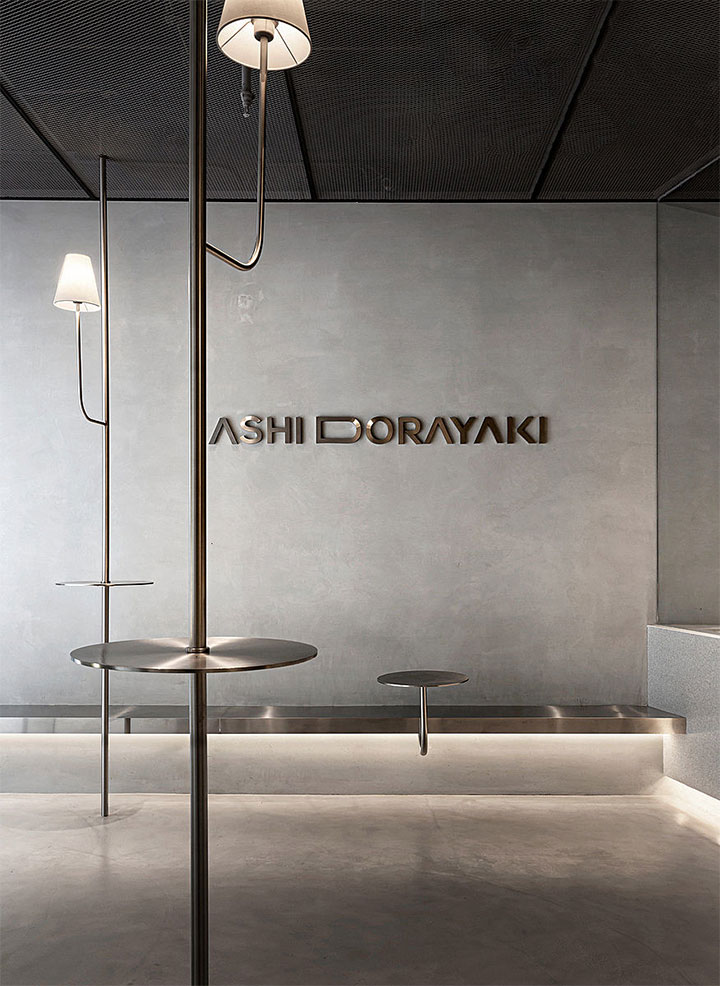 Minimalist restaurant interior with simple tables attached to ceiling-high poles