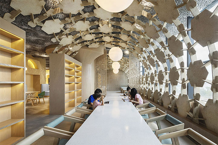 Children's restaurant design with abstract-shaped wood boards as ceiling treatment