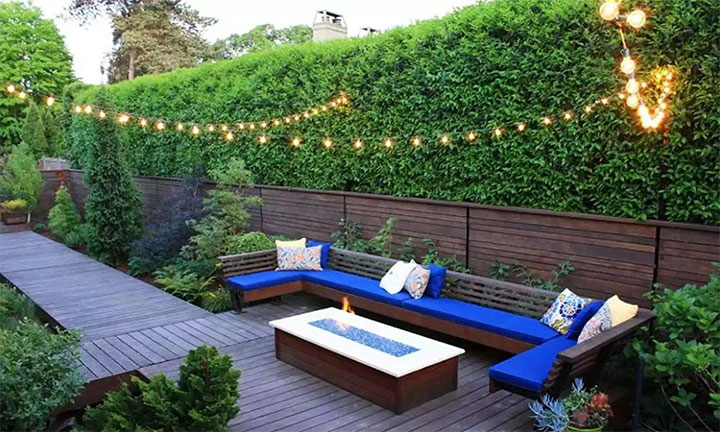 Tall artificial boxwood panels creating a privacy wall in outdoor area