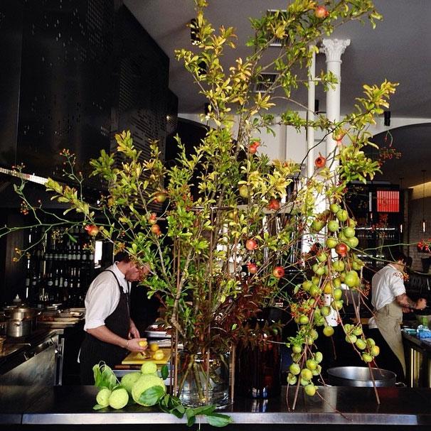 Fruit tree branches used in restaurant flower arrangements