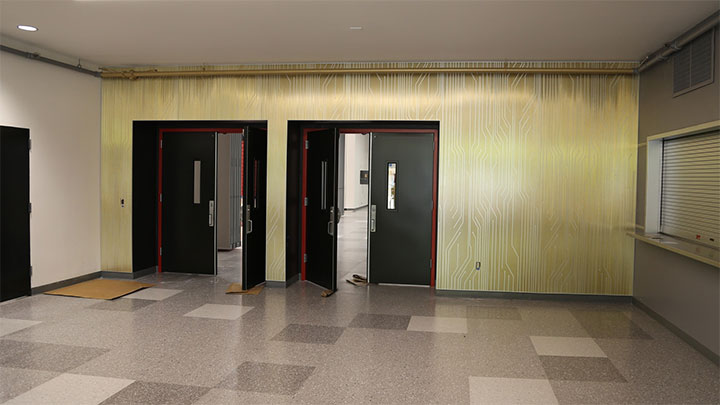 Engraved metal sheets used as wall finish in highschool interior design