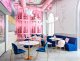 Pink shelf and blue upholstery in restaurant dining area